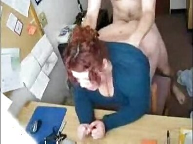 Chubby redhead gets fucked on top of her office desk